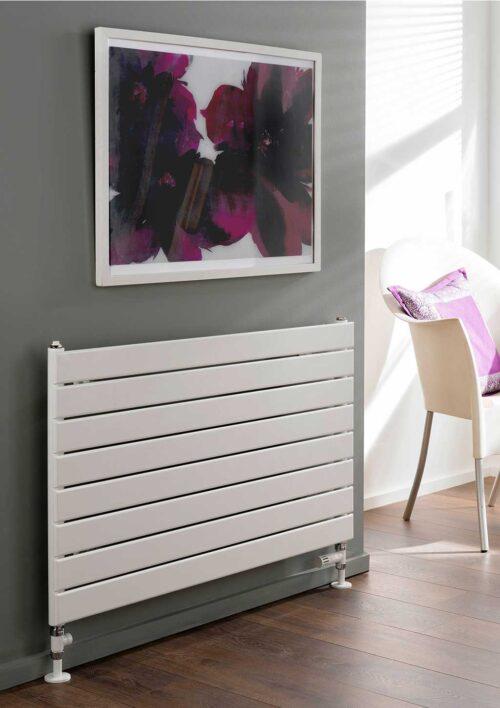 Flat panel radiator benefits; all white horizontal radiator placed below an art piece