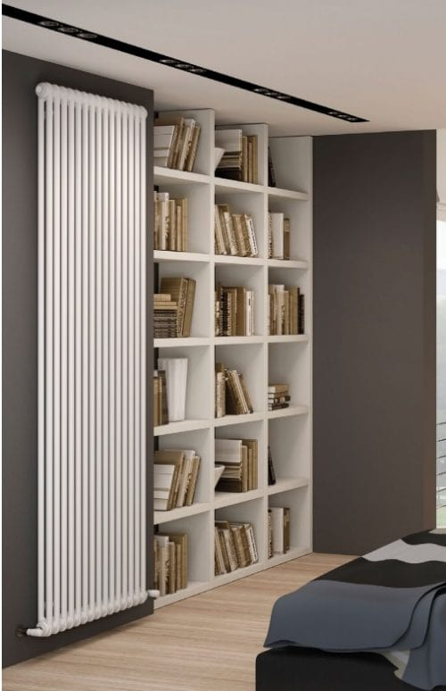 Guide to different radiator materials; All white vertical designer radiator installed next to an all white bookshelf