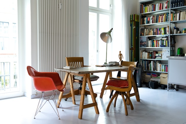 Replace old radiator; living room sporting a white radiator, a bookshelf and a study table with chairs