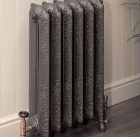 Guide to different radiator materials; grey cast iron radiator placed against a white wall