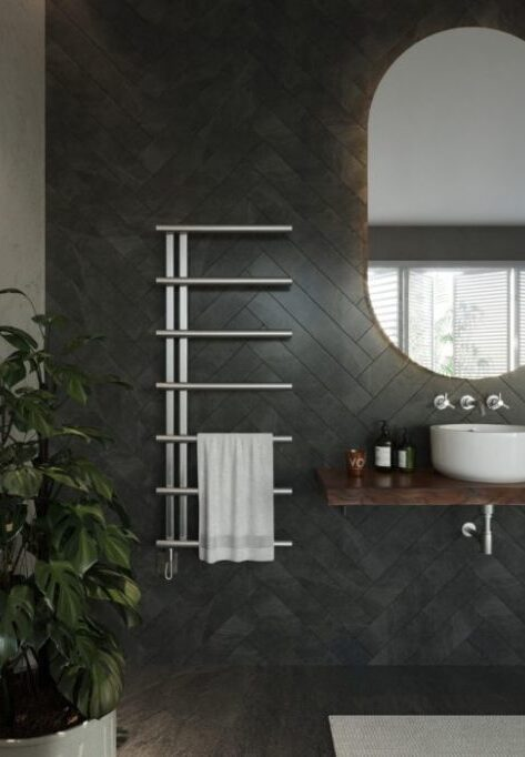 Guide to different radiator materials; stainless steel towel radiator installed on a patterned bathroom wall