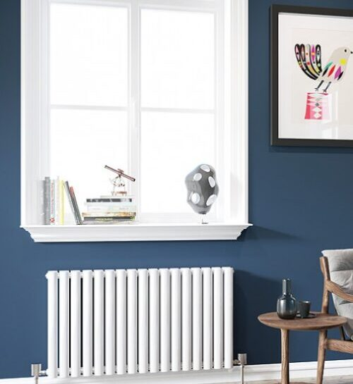 an all white horizontal radiator installed under a window with a side table next to it