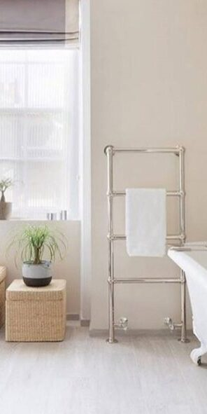 compact radiators for home; stainless steel towel rail installed next a bath tub with towel on it